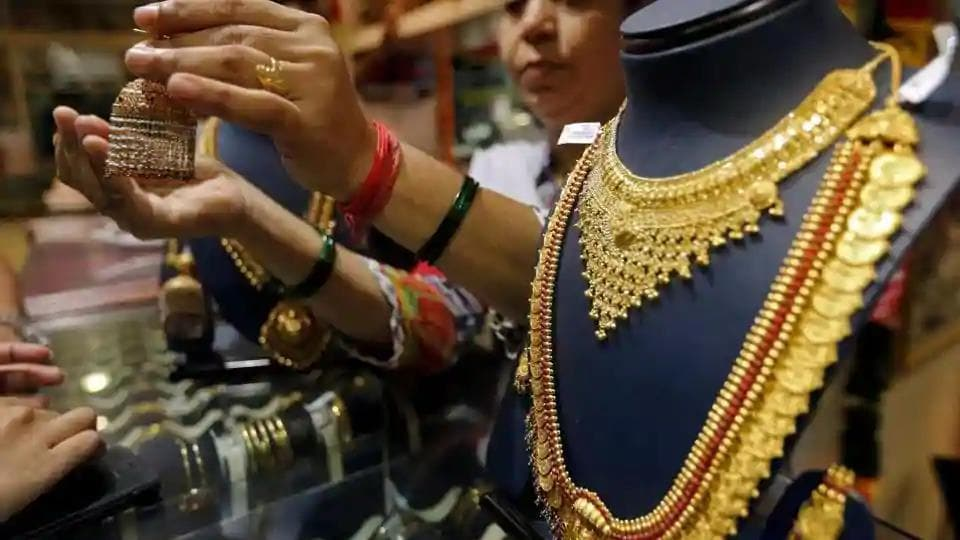 A saleswoman shows a gold earring to customers at a jewellery showroom in Mumbai.