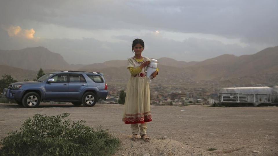 An Afghan girl poses for a photograph as she sells tea on hilltop in Kabul, Afghanistan.