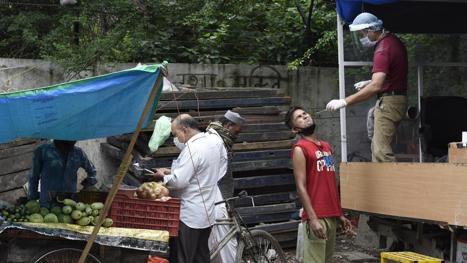 A man purchases vegetables while a health worker collects a swab sample from a man opposite him, in New Delhi on July 25. In contrast with the number of tests conducted over the week but in line with weekend figures, fewer tests were conducted on July 26 at 17,522. Delhi is currently just a fraction short of completing a million tests. (Arvind Yadav / HT Photo)