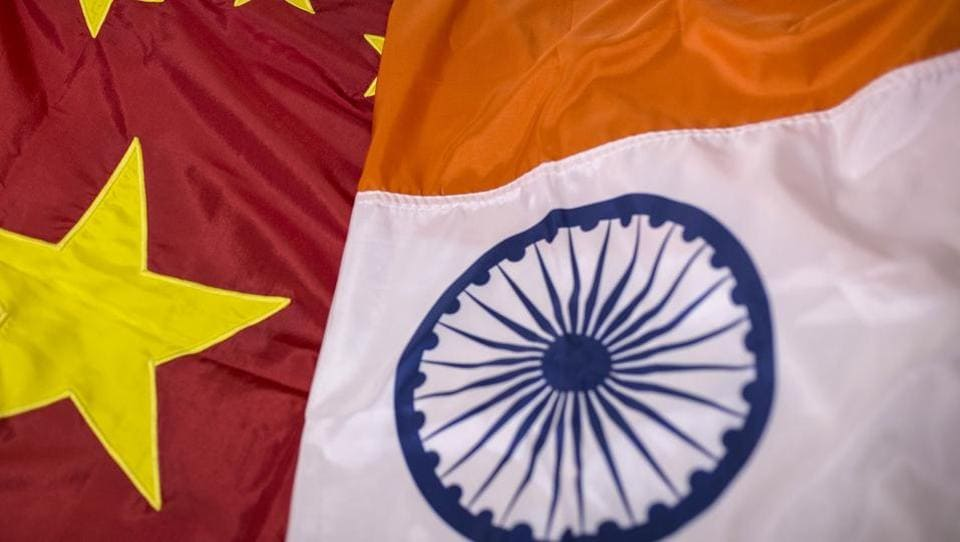 A Chinese national flag, left, and an Indian national flag are arranged for a photograph at FlagSource workshop in Mumbai.