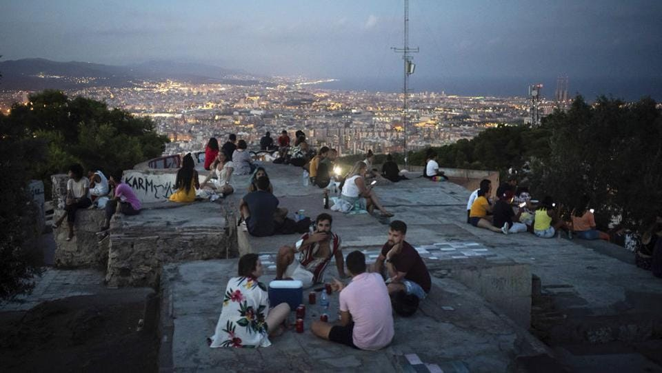 People gather outdoors at dusk on a viewpoint in Barcelona on July 25. While families and the at-risk elderly are mostly complying with rules to wear face masks and maintain a 1.5 metre distance from others, teenagers and young adults in many of Spain's cities have been completely flouting the health rules and guidelines, AP reports. (Felipe Dana / AP)