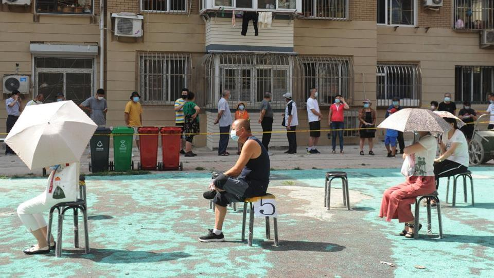 People sit socially distanced on chairs as they wait to undergo coronavirus tests at a makeshift testing centre in Dalian, China on July 28. A fresh coronavirus cluster in Dalian has spread to other provinces and prompted fresh restrictions, authorities told AFP.  (STR / AFP)