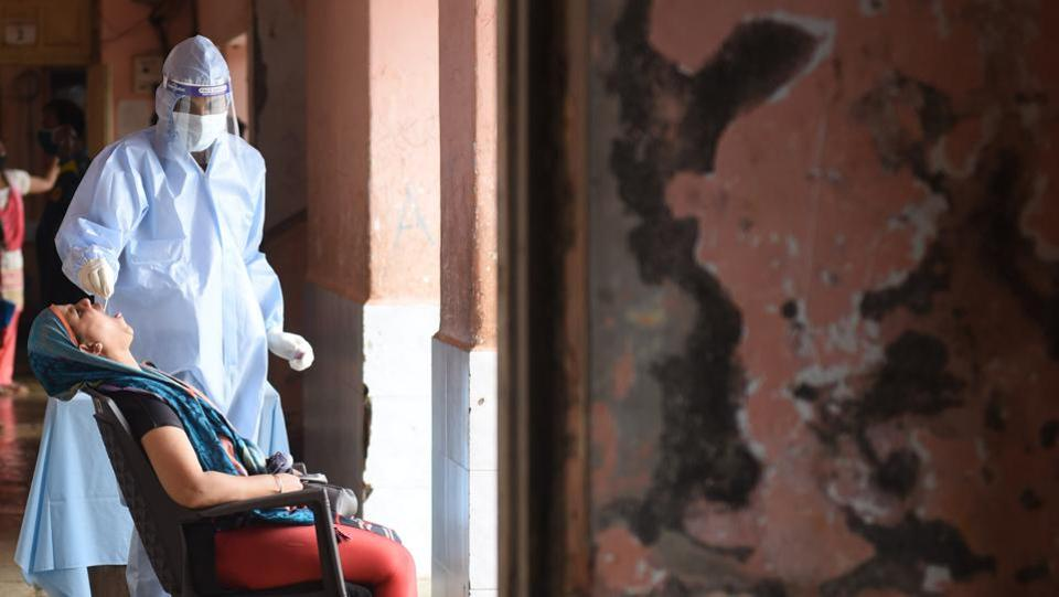 A Brihanmumbai Municipal Corporation (BMC) health care worker collects swab sample from a woman to test for Covid-19 infection at Anushakti Nagar in Mumbai on July 28. Maharashtra continues to grapple with the highest Covid-19 casualties across India, apart from having the largest number of infections. (Satish Bate / HT Photo)