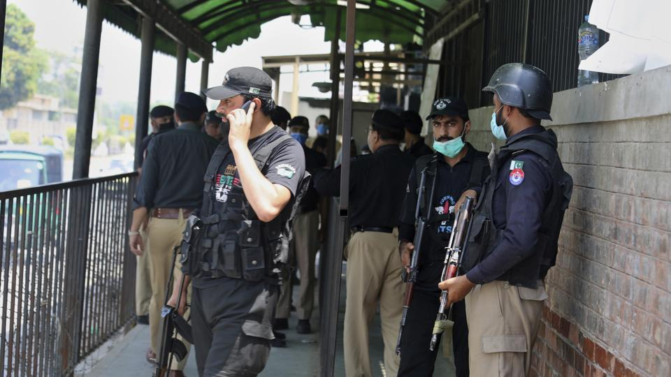 Police officers gather at an entry gate of district court following the killing of Tahir Shamim Ahmad, who was in court accused of insulting Islam, in Peshawar, Pakistan.