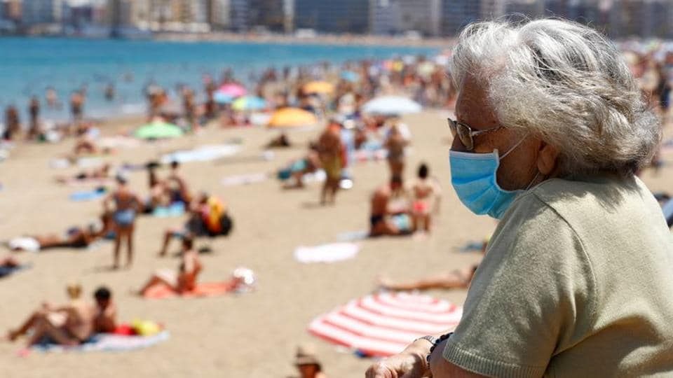 A woman wearing a face mask watches people sunbathing on the Las Canteras beach in Las Palmas de Gran Canaria, the island of Gran Canaria, Spain May 31, 2020.