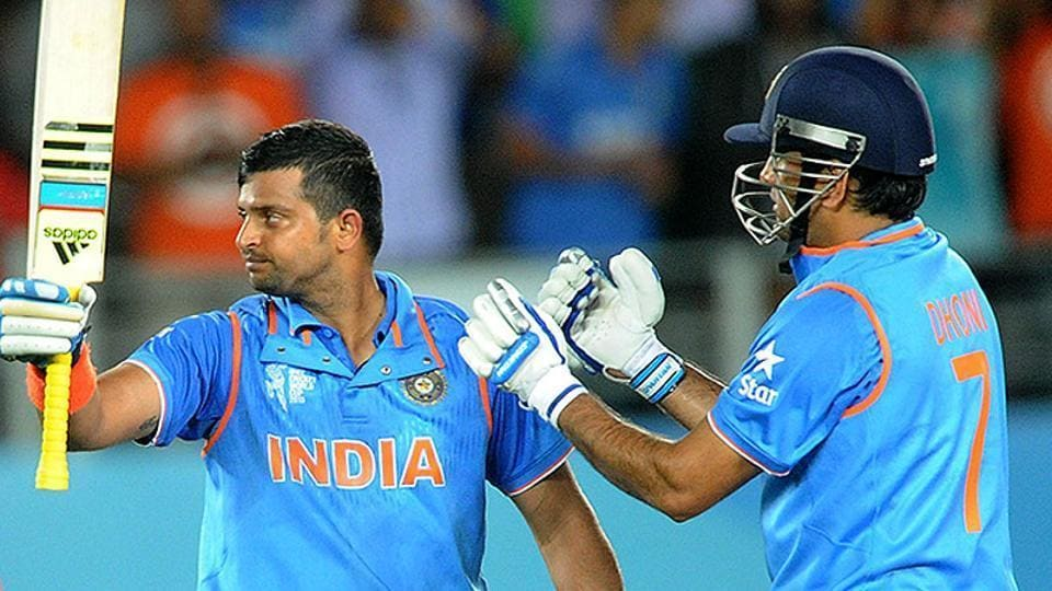 India's Suresh Raina waves his bat as his captain MS Dhoni watches after scoring a century while batting against Zimbabwe during their Cricket World Cup Pool B match.