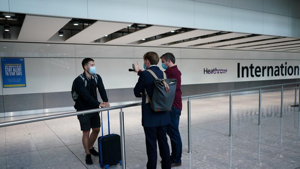 Reporters speak to a traveller arriving from Madrid at the Terminal 5 at Heathrow Airport, as the spread of the coronavirus disease (COVID-19) continues, in London, Britain.