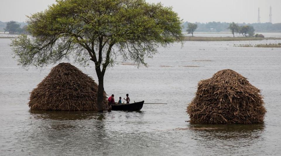 A woman with two children rows a small boat in a flooded field in Bhagalpur district of Bihar, July 28, 2020.
