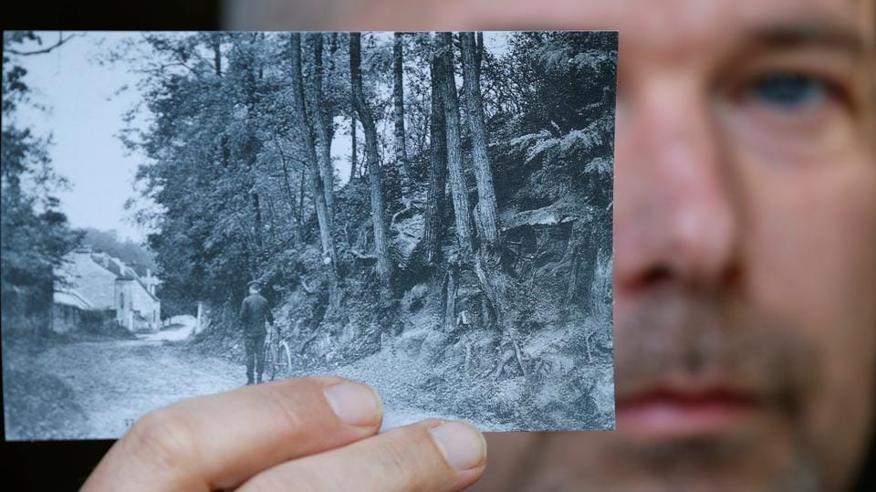 Researcher Wouter van der Veen, scientific director at the Institut Van Gogh, shows a copy of the postcard (around 1905-1910) which enabled him to identify the location that inspired Dutch painter Vincent van Gogh for his last work 'Tree Roots' (1890), painted shortly before his death in Auvers-sur-Oise near Paris, on July 29.  (Christian Hartmann / REUTERS)