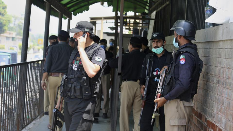 Police officers gather at an entry gate of district court following the killing of Tahir Naseem, who was accused of insulting Islam, in Peshawar, Pakistan, Wednesday, July 29, 2020.