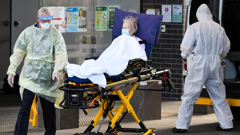 Medical workers evacuate a resident from the Epping Gardens aged care facility in Melbourne on July 30. Australia on July 30 reported a record number of new coronavirus infections following a spike in cases at elderly-care homes. (William West / AFP)