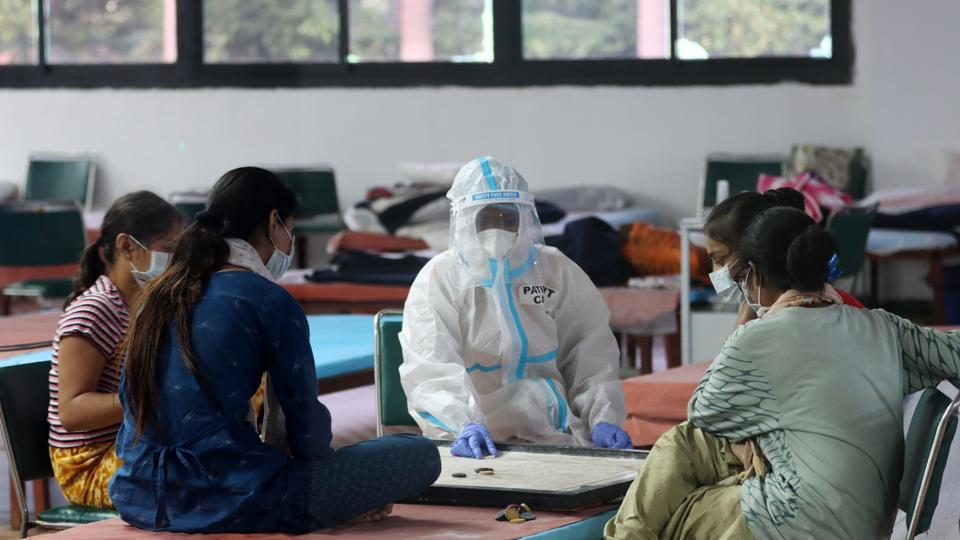 A health worker wearing personal protective equipment (PPE) plays a game of carrom with patients in a women's ward at the Commonwealth Games (CWG) Village Sports Complex Covid-19 Care Centre in New Delhi on July 30. The number of people who have recovered from the coronavirus disease (Covid-19) in India crossed the 1 million mark on July 29. (T. Narayan / Bloomberg)