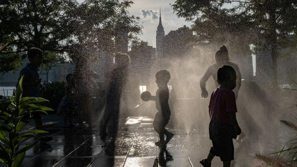 Children cool off in a fountain while enjoying a warm and humid day at Gantry Plaza State Park following the outbreak of the coronavirus disease (COVID-19), in Long Island City, New York, U.S., July 25, 2020.
