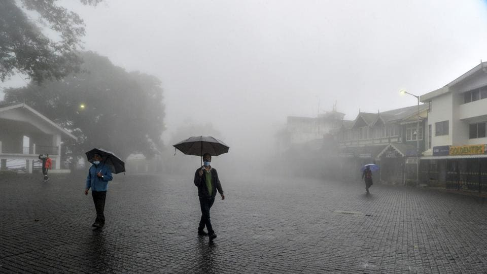 People wearing face masks cross an empty square at the Chowrasta Mall amid heavy fog during lockdown in Darjeeling on July 29. Despite daily cases rising by 50,000 for two days in a row now, there has also been a consistent trend of more than 30,000 recoveries being logged over the last eight days, HT reported. Average daily recoveries have risen from around 15,000 in the first week of July to around 35,000 in its last week. (Diptendu Dutta / AFP)