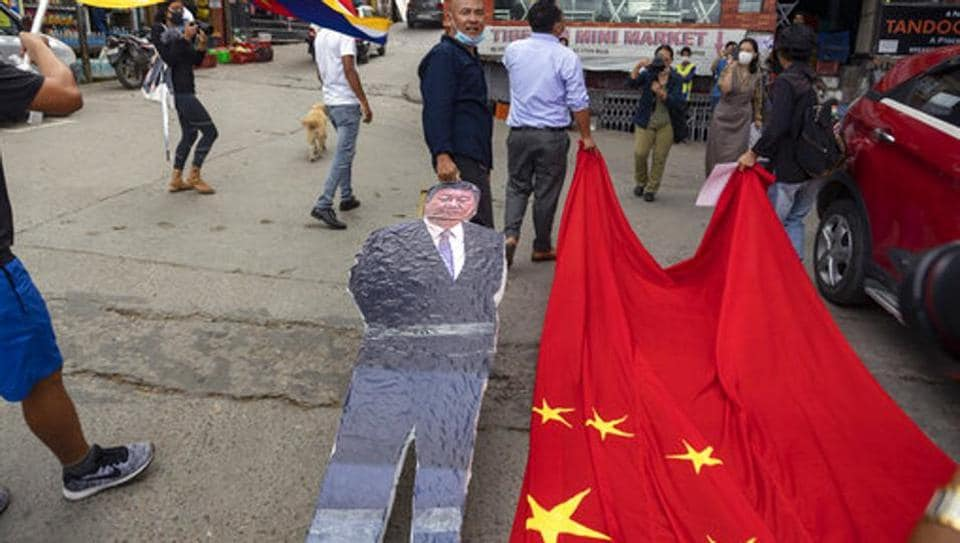 Members of the Tibetan Youth Congress drag a Chinese flag and a cutout of Chinese President Xi Jinping during a street protest calling for the boycott of Chinese goods in Dharmsala, India.