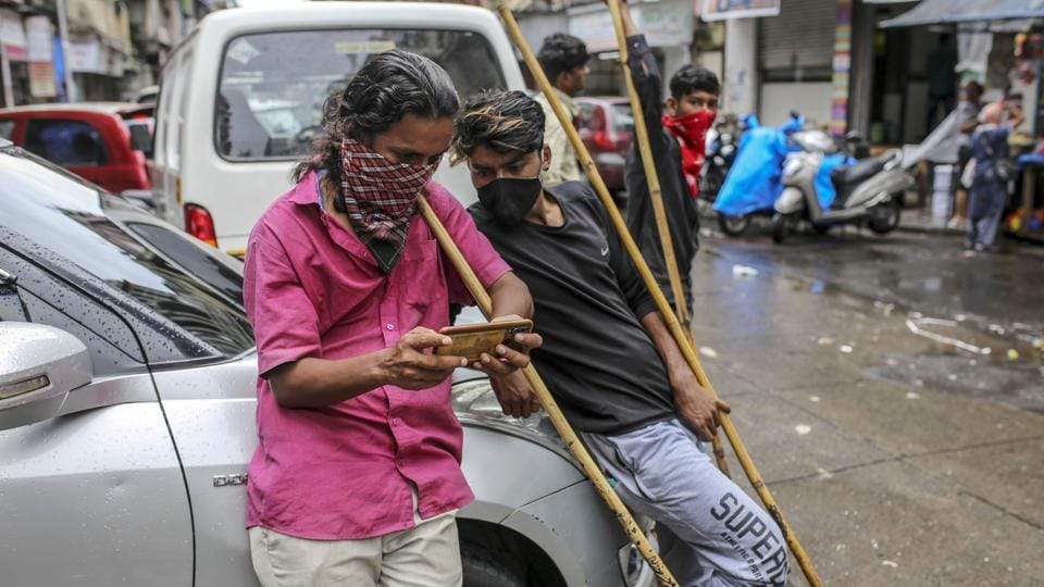 Daily laborers wearing face coverings and protective masks look at a mobile phone while waiting for work in Mumbai.