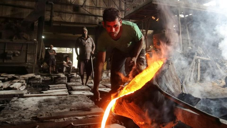 A worker pours molten iron from a ladle to make automobile spare parts inside an iron casting factory in Ahmedabad.