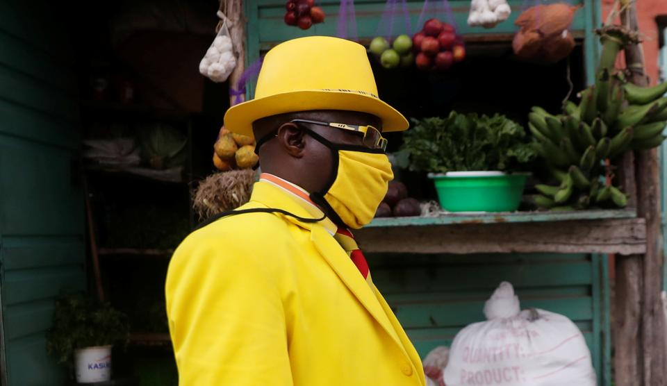 James Maina Mwangi walks along a street as he displays his attire comprising at least 160 suits with matching accessories including a mask to prevent the coronavirus disease (COVID-19) infection, near his residence in Nairobi, Kenya July 30, 2020. (REUTERS)