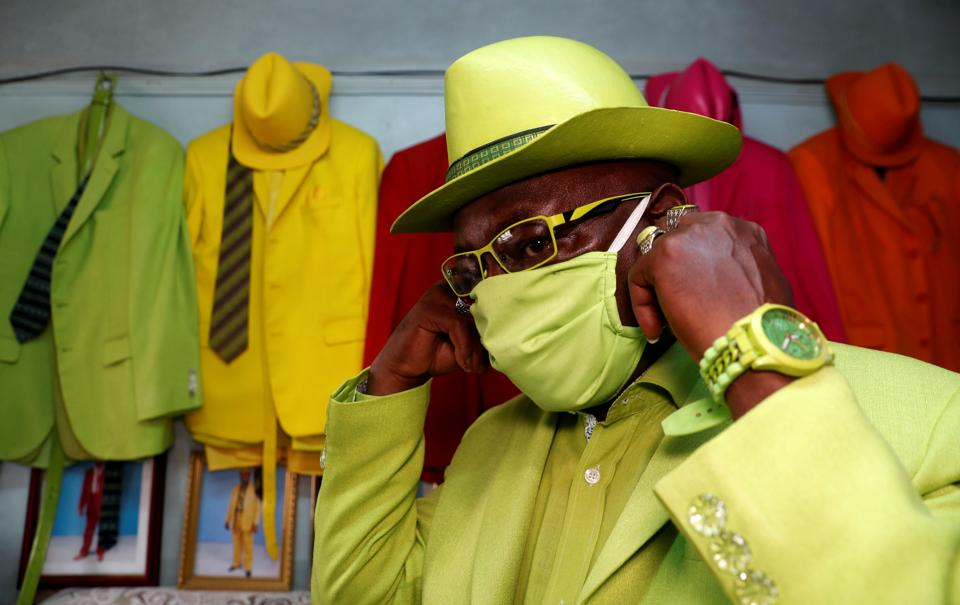 James Maina Mwangi adjusts his mask while posing for a photograph as he displays his attire comprising at least 160 suits with matching accessories including a mask to prevent the coronavirus disease (COVID-19) infection at his residence in Nairobi, Kenya July 30, 2020.  (REUTERS)