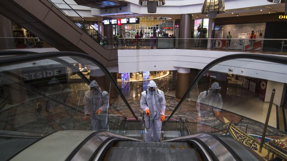 A man in personal protective equipment(PPE) sprays disinfectant inside a shopping mall premises as part of an Unlock 3 reopening in Mumbai on July 30. 64.5% of all Covid-19 patients have now recovered  across India as the country moves towards the third stage of its graded unlocking from August 1. This is higher than the global average of 61.9%. (Pratik Chorge / HT Photo)