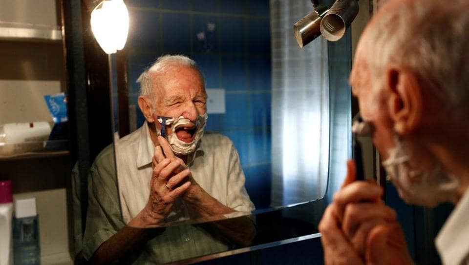 Giuseppe Paterno, 96, Italy's oldest student, shaves his beard as he gets ready for the day, two days before he graduates from The University of Palermo with an undergraduate degree in history and philosophy, at his home in Palermo, Italy, July 27, 2020.