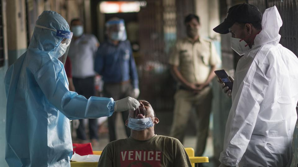 A doctor collects swab during covid-19 health check up camp at Isolation centre in Mumbai.