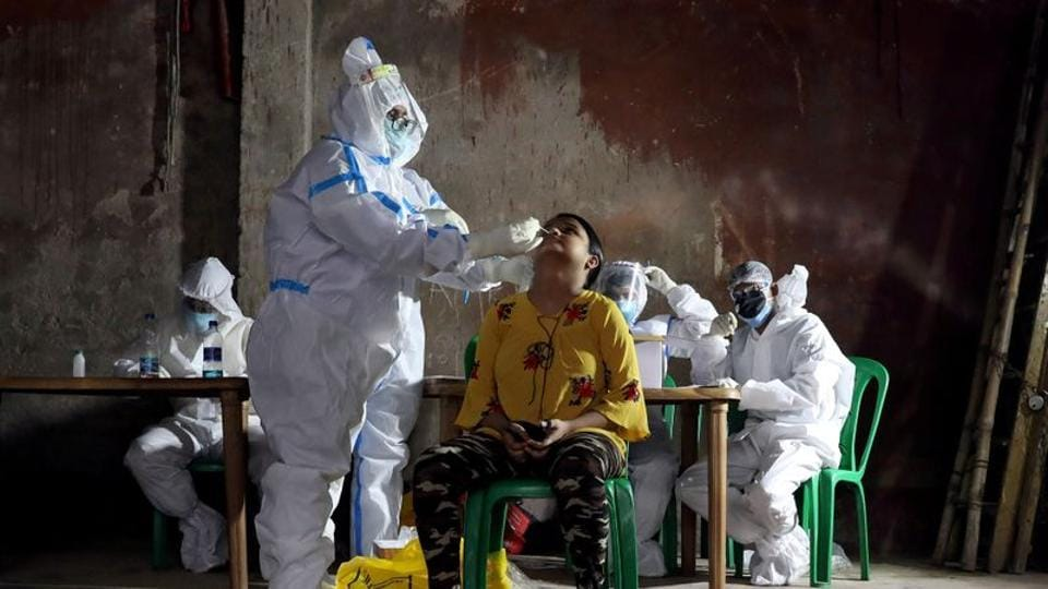 A healthcare worker wearing personal protective equipment (PPE) takes swab from a woman to test for the coronavirus disease  in Kolkata.