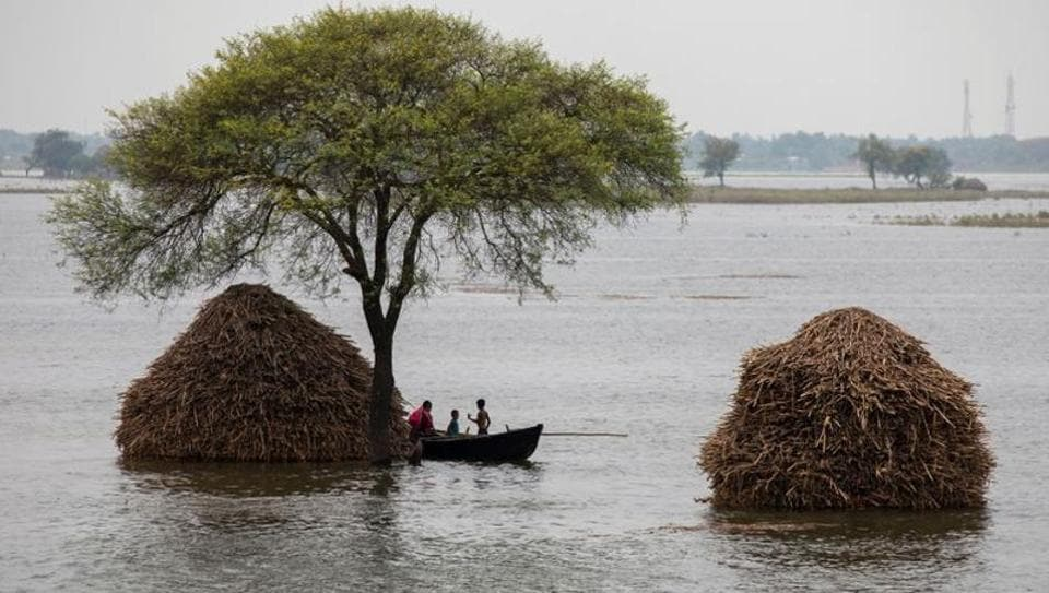 A woman with two children rows a small boat in a flooded field in Bhagalpur district in Bihar.