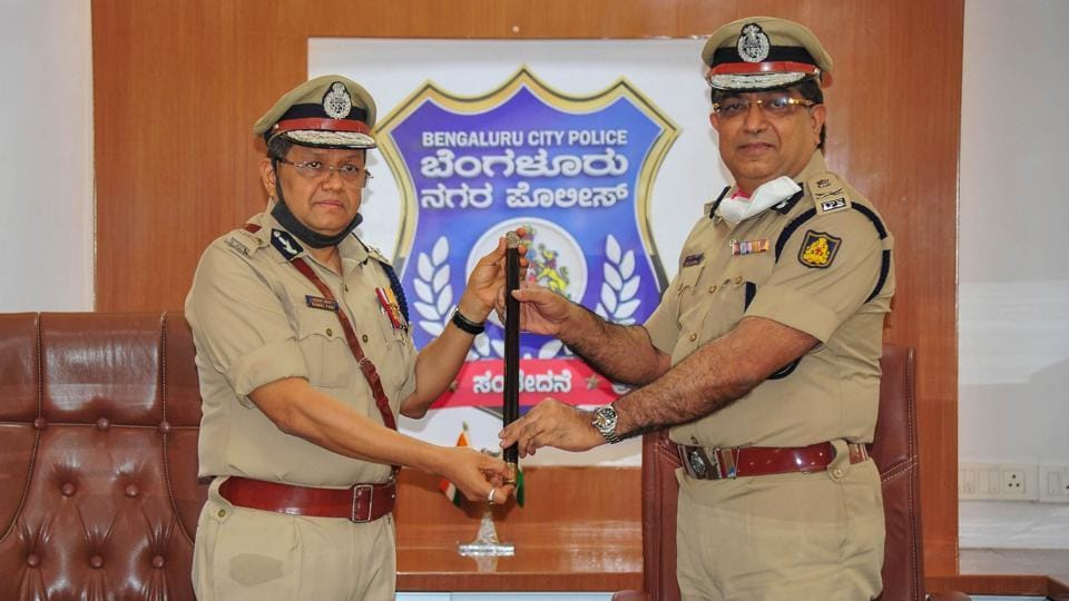 Outgoing Police Commissioner Bhaskar Rao (R) hands over a baton to the newly appointed Bengaluru City Police Commissioner Kamal Pant at commissioner office, in Bengaluru, Saturday, Aug. 1, 2020.
