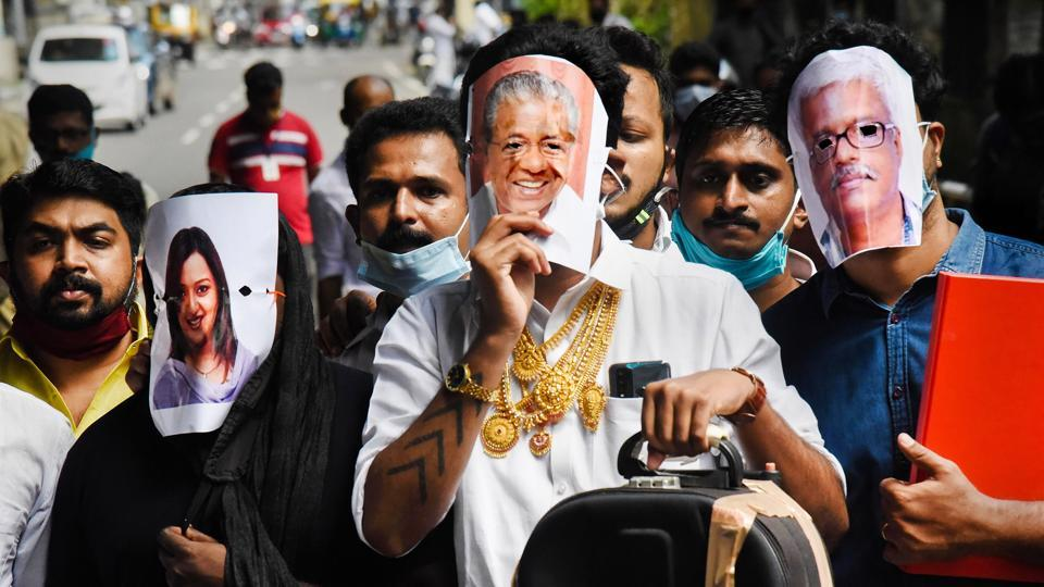 Youth Congress activists hold pictures of Kerala Chief Minister Pinarayi Vijayan (C), former UAE consulate officer Swapna Suresh (L), and State IT Secretary M Sivasankar (R) during a protest over the Kerala gold smuggling case, in Kochi.