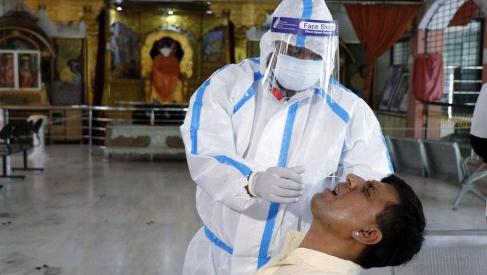 A healthcare worker wearing personal protective equipment takes a swab from a man to test for Covid-19  in Ahmedabad, Gujarat.