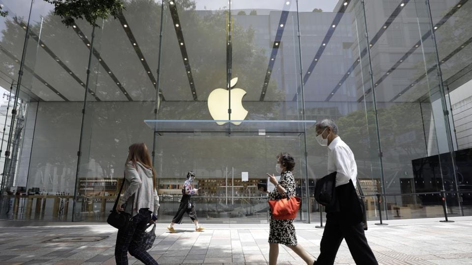 Pedestrians wearing protective masks walk past an Apple Inc. store in the Omotesando district of Tokyo, Japan.