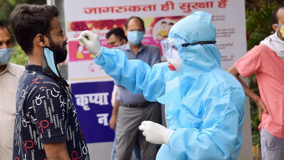 A medic takes swab samples from a man for Covid-19 testing at a collection centre at Hotel Pataliputra Ashoka in Patna.