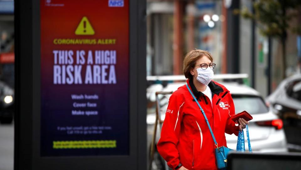 A woman wearing a protective mask walks past a warning sign in Manchester, as the city and the surrounding area faces local restrictions in an effort to avoid a local lockdown being forced upon the area, amid the coronavirus disease (COVID-19) outbreak, Britain, August 1, 2020. (Representational)