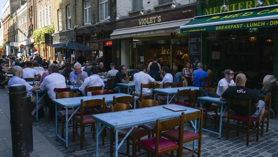 Public sit at the outside tables of restaurants in Soho, in London on Friday.