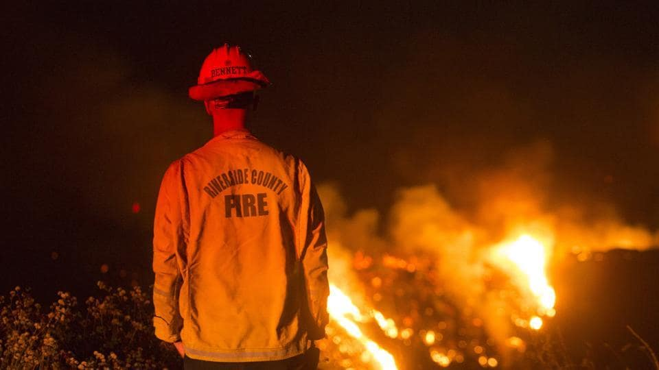 A firefighter watches a brush fire at the Apple Fire in Banning, California, on Saturday.
