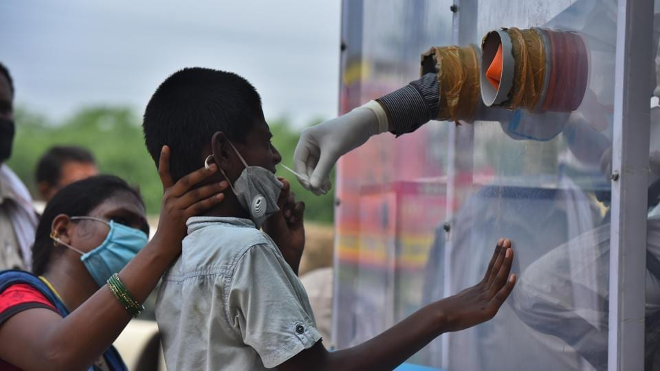 A health worker collects a swab sample from a boy for Covid-19 rapid antigen testing from inside a mobile kiosk, at New Ashok Nagar in New Delhi on Saturday.