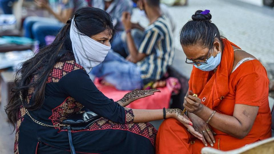 A woman gets her palms and arms decorated with 'mehndi' on the eve of Raksha Bandhan festival, during Unlock 3.0, in New Delhi, Sunday. (PTI Photo/Manvender Vashist)