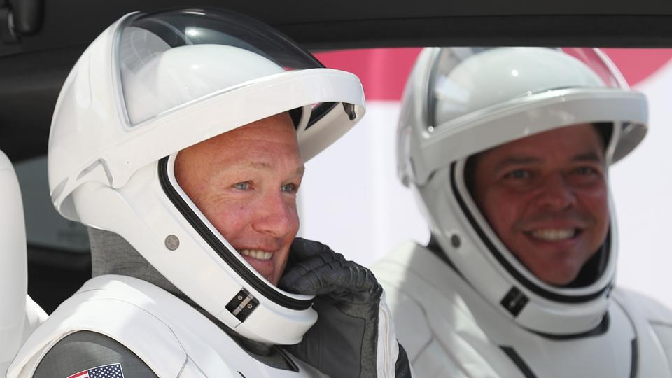 File photo of NASA astronauts Bob Behnken (R) and Doug Hurley in a Tesla vehicle.