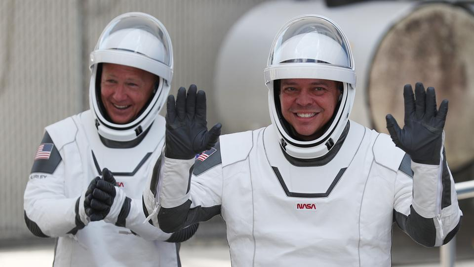 Nasa astronauts Bob Behnken (R) and Doug Hurley walking out of the Operations and Checkout Building on their way to the SpaceX Falcon 9 rocket with the Crew Dragon spacecraft on launch pad 39A at the Kennedy Space Center in Cape Canaveral, Florida on May 30, 2020