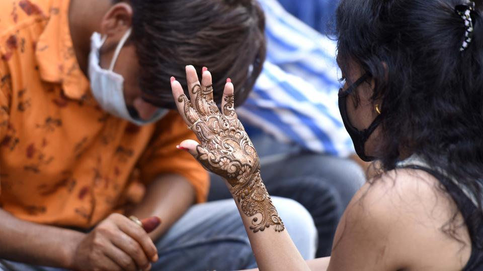 A woman has henna (mehendi) applied to her forearms on the eve of Rakshabandhan festival at Sadar Bazar, in Gurugram, India, on Sunday, August 02, 2020.  (Parveen Kumar/Hindustan Times)