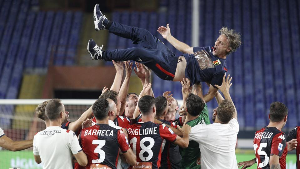 Genoa players celebrate at the end of the match with coach Davide Nicola.