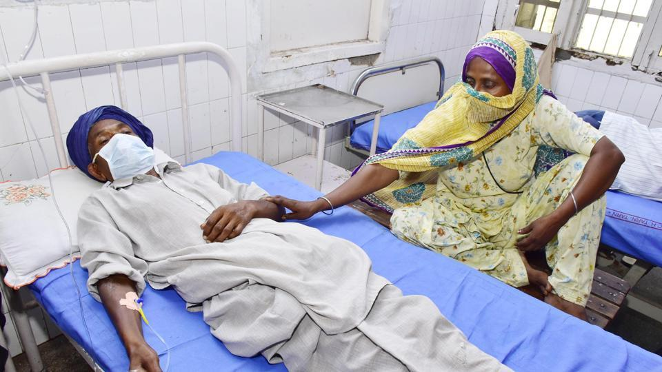 A family member next to a patient who is undergoing treatment after allegedly drinking spurious alcohol, at Civil hospital in Tarn Taran, Punjab. (Photo by Sameer Sehgal/ Hindustan Times)