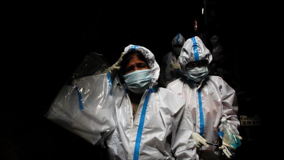 A health worker in personal protective equipment reacts as she and the rest of the team walk through an alley during a check up campaign for the coronavirus disease (Covid-19) at a slum area in Mumbai.