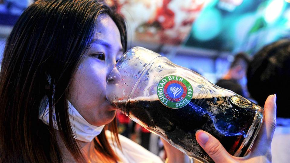 This photo taken on August 1, 2020 shows a woman drinking a beer during the annual Qingdao Beer Festival in Qingdao, in China's eastern Shandong province. - Thousands of Chinese beer lovers left their facemasks and virus worries behind to gather in large crowds and raise a much-needed glass as the annual Qingdao beer festival opened over the weekend.