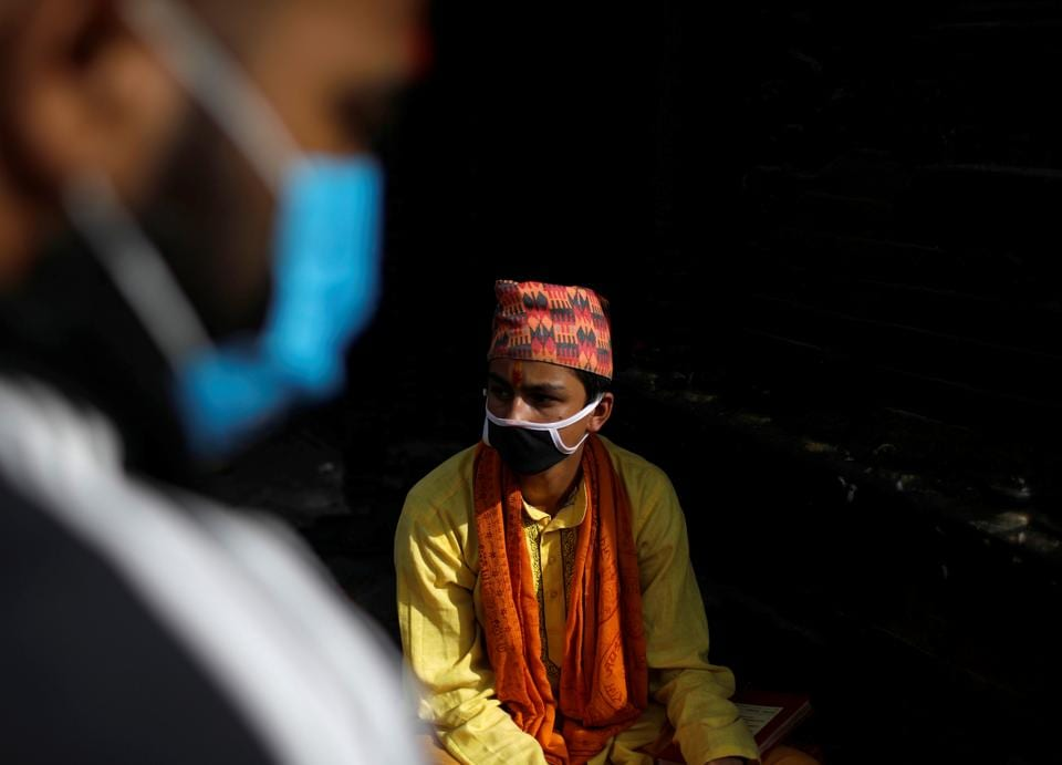 A Hindu priest wearing a face mask waits for devotees during the Janai Purnima festival (Sacred Thread Festival) at Pashupatinath Temple amid the outbreak of the coronavirus disease (COVID-19) in Kathmandu, Nepal, August 3, 2020. Hindus take holy baths and change their sacred thread, also known as Janai, for protection and purification, during the festival.  (REUTERS)