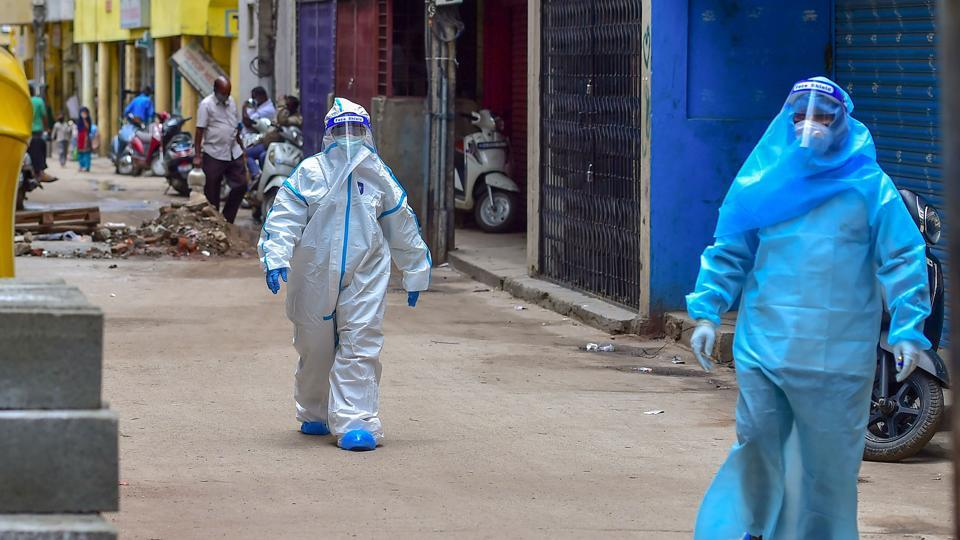 Medics wearing PPE kits arrive to conduct COVID-19 Rapid Antigen test at Kalasipalyam during a week lockdown imposed due to surge in coronavirus cases, in Bengaluru.