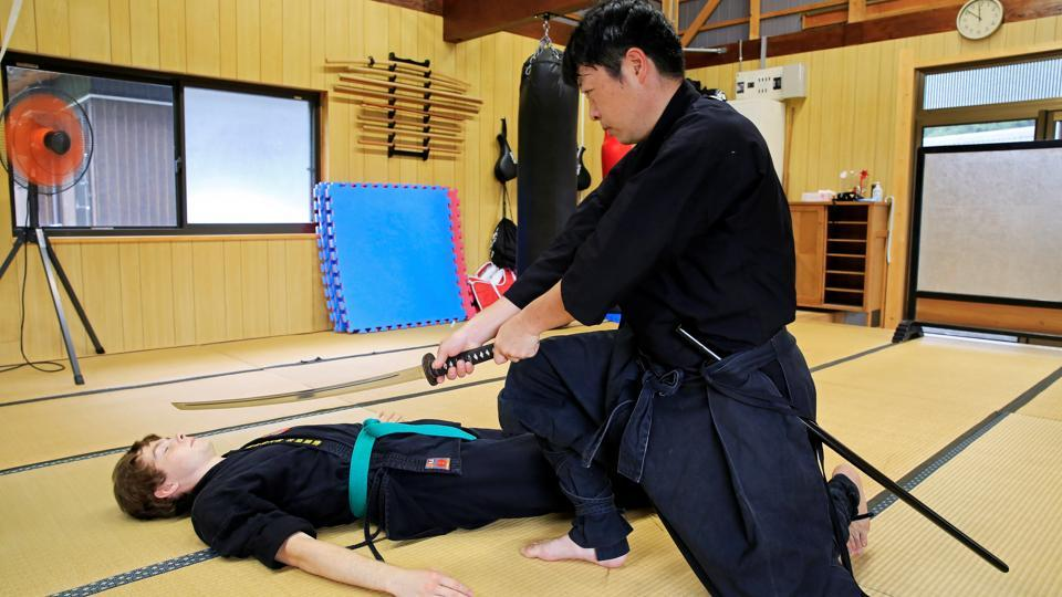 Genichi Mitsuhashi, 45, the first person to hold a degree from Mie University's graduate course on ninja studies, teaches martial arts to a guest in a training hall next to his home in Iga, Mie Prefecture, central Japan July 30, 3020.