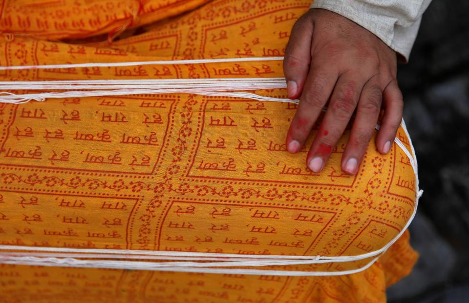 A Hindu priest puts sacred threads on his lap as he waits for devotees during the Janai Purnima festival (Sacred Thread Festival) at Pashupatinath Temple in Kathmandu, Nepal, August 3, 2020.  (REUTERS)