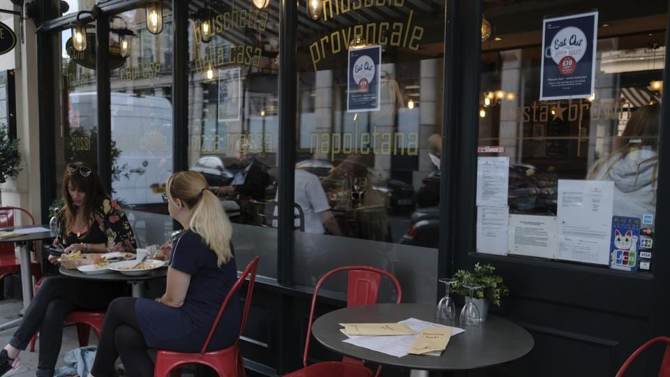 Customers eat at restaurant next to signs indicating discounts off food, in central London.